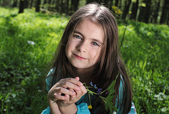 Girl in the Grass with a Flower - Pediatric Dentist and Orthodontics in Chicopee, Springfield and Ludlow, MA